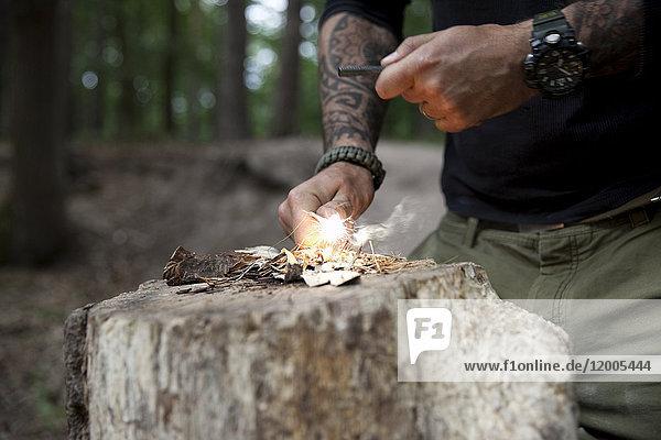 Mann entzündet ein Feuer auf Baumstumpf im Wald