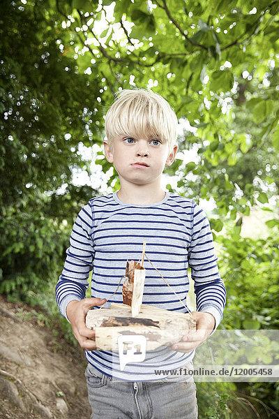 Junge mit geschnitztem Holzboot im Wald