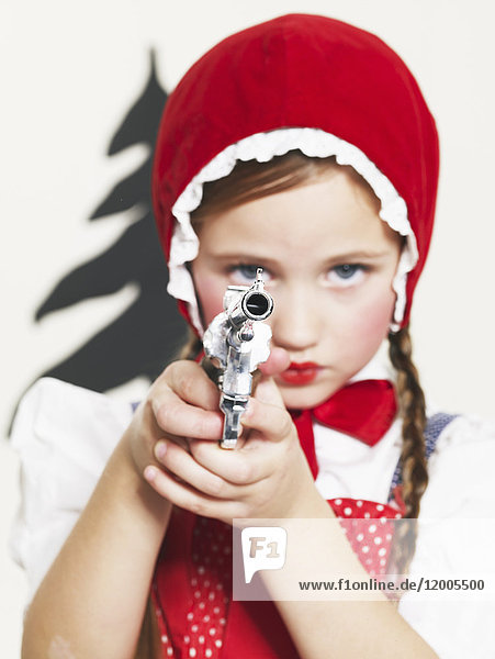 Little girl dressed up as Red Riding Hood holding pistol