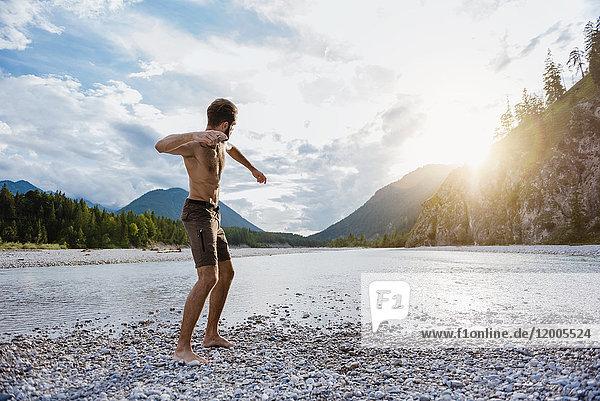 Deutschland  Bayern  Mann am Flussufer mit Steinwurf