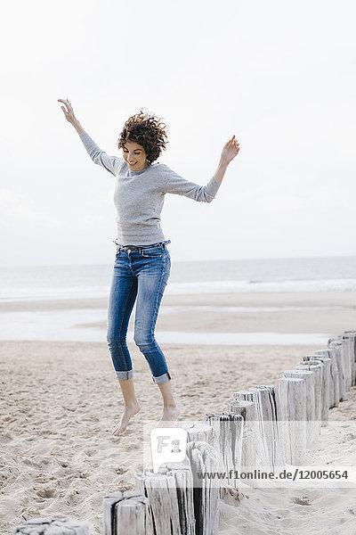 Glückliche Frau beim Springen am Strand