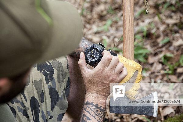 Nahaufnahme des Mannes mit Axt im Wald bei der Zeitkontrolle
