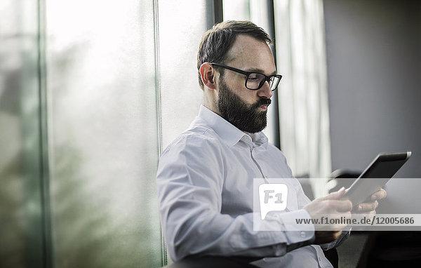 Geschäftsmann liest auf digitalem Tablett  sieht besorgt aus