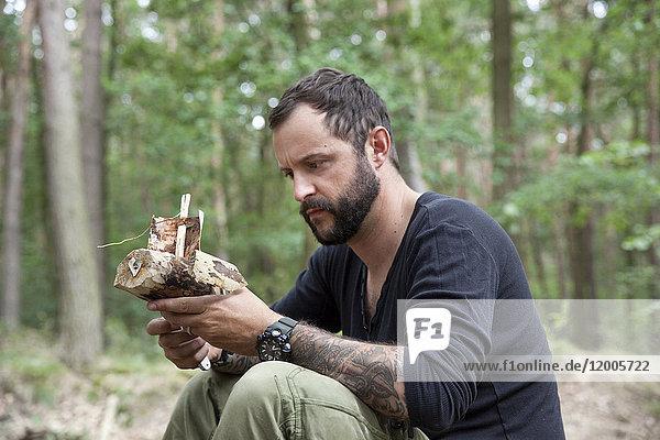 Mann schaut auf geschnitztes Holzboot im Wald