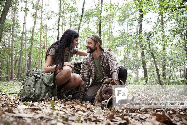 Paar mit Rucksack und Hund im Wald