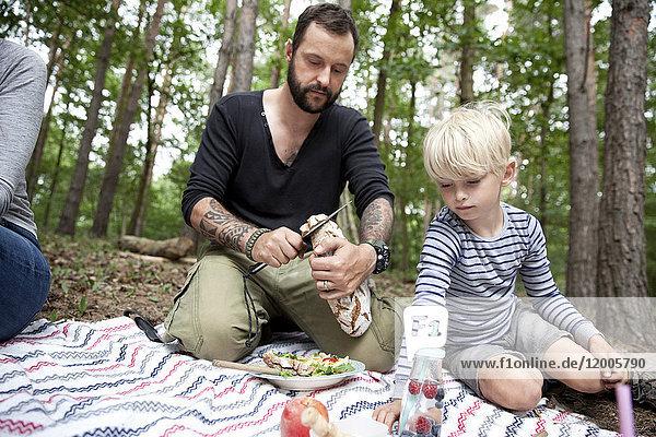 Mann beim Brotschneiden beim Picknick im Wald