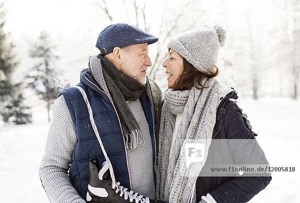 Seniorenpaar mit Schlittschuhen in der Winterlandschaft