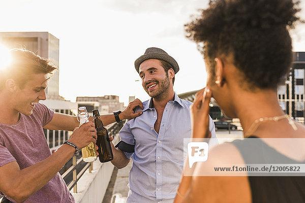 Freunde klirren Bierflaschen auf einer Dachparty