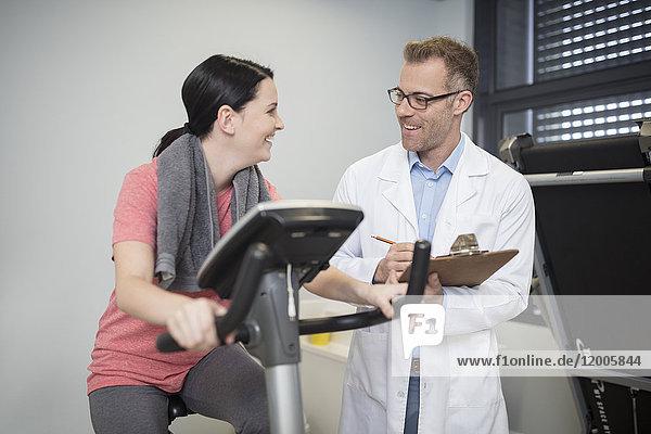 Lächelnder Arzt und Patient am Trainingsgerät