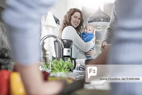 Mutter und Baby in der Küche beim Kochen