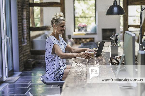 Frau in der Küche sitzend  mit Laptop