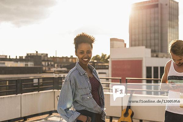 Porträt einer lächelnden jungen Frau auf einer Dachparty