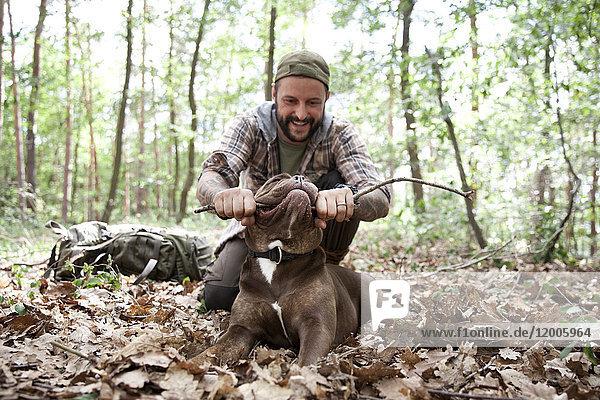 Mann spielt mit Hund im Wald