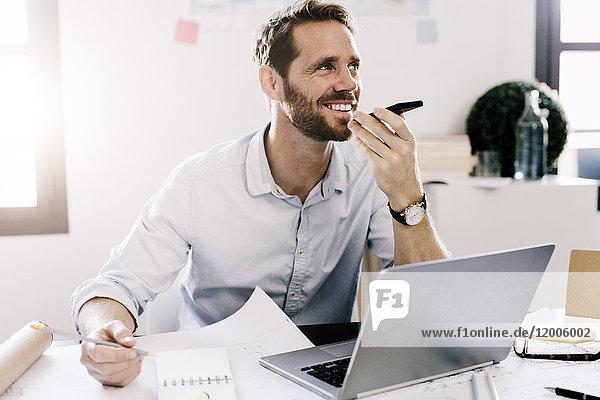 Lächelnder Geschäftsmann mit Handy im Büro