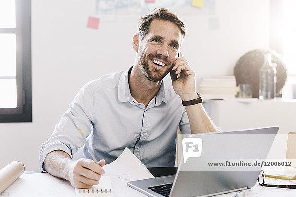 Lächelnder Geschäftsmann am Telefon in seinem Büro