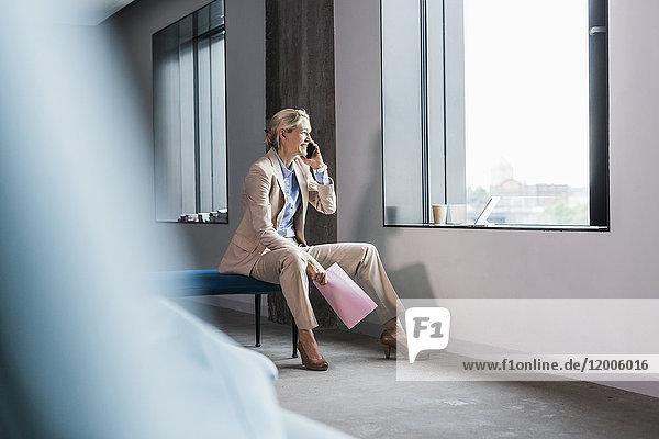 Lächelnde Geschäftsfrau am Telefon sitzend am Fenster