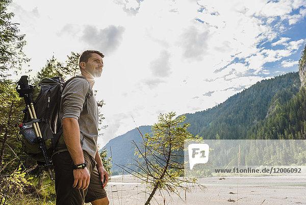 Deutschland  Bayern  junger Wanderer mit Rucksack auf Distanz