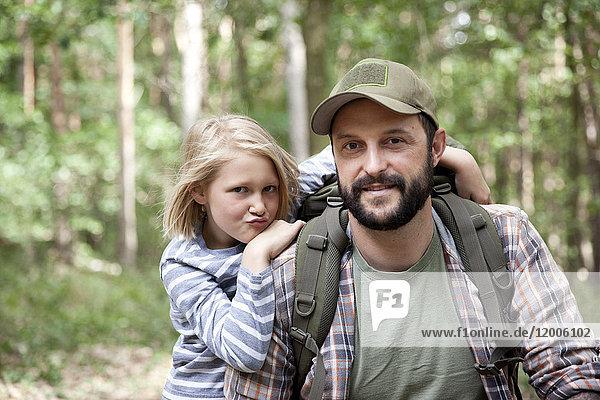 Porträt von lächelndem Vater und Tochter im Wald