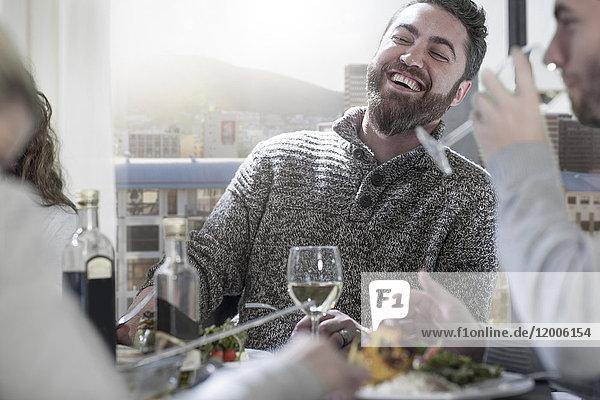 Mann lacht am Esstisch mit Freunden