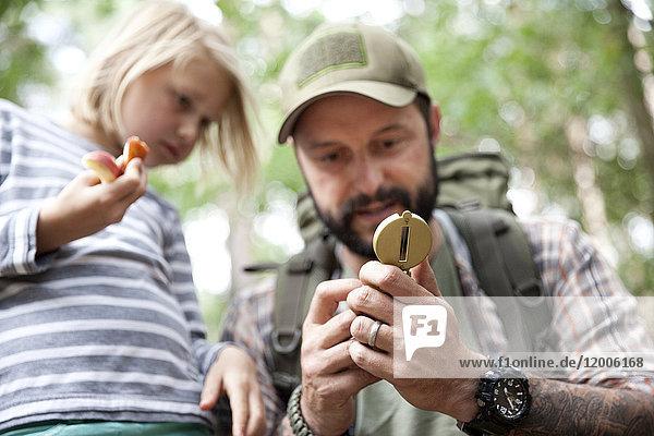 Vater zeigt Kompass an Tochter im Wald