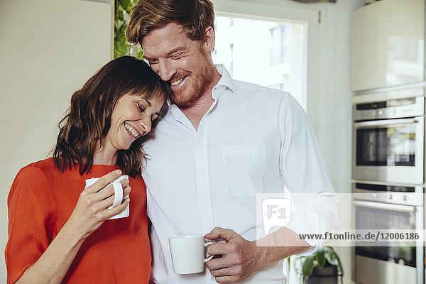 Glückliches Paar in der Küche mit Kaffeebechern