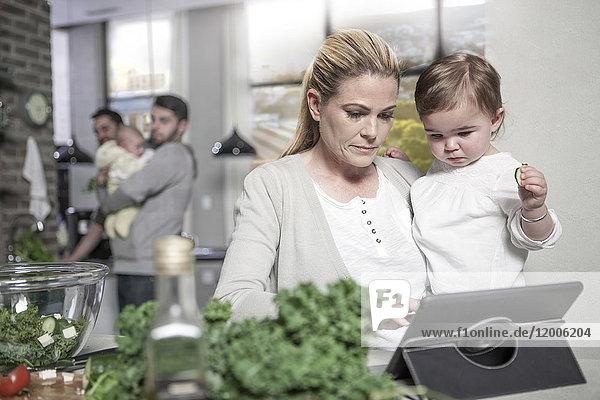 Mutter hält Baby mit Tablette in der Küche