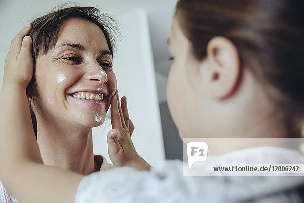 Tochter legt Gesichtscreme auf das Gesicht der Mutter