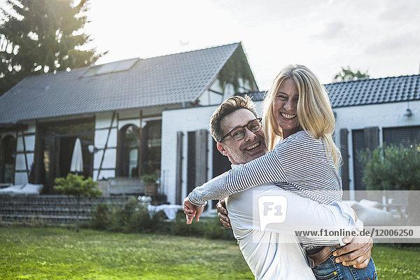 Ein glückliches Paar  das sich im Garten seines Landhauses umarmt.