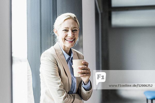 Porträt einer glücklichen Geschäftsfrau mit Kaffee am Fenster