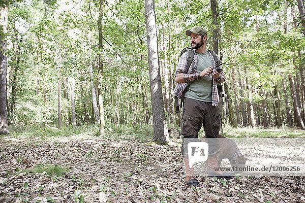 Mann mit Hund auf einer Wanderung im Wald per Handy