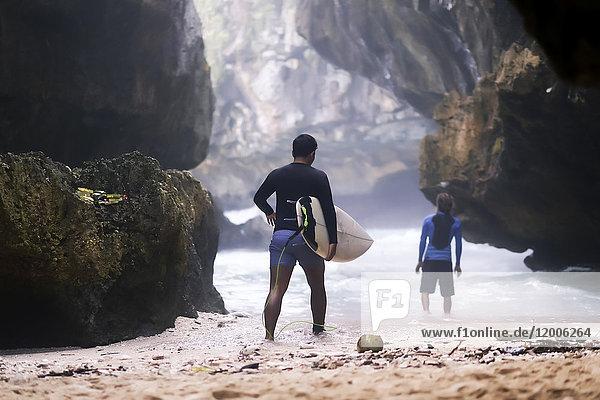 Indonesien  Bali  Rückansicht Surfer mit Surfbrett