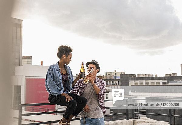 Junges Paar klirrende Bierflaschen auf dem Dach