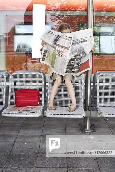 Little girl sitting at platform reading newspaper