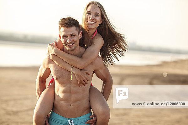 Mann  der seine Freundin huckepack am Strand trägt.