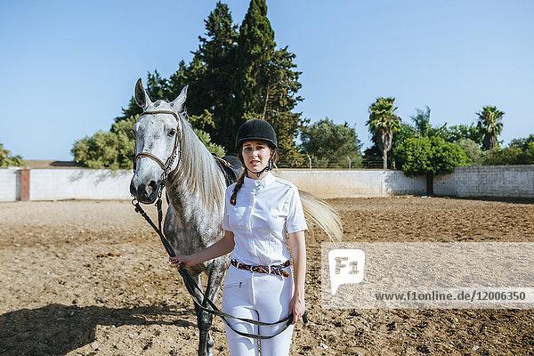 Junger Reiter mit Pferd auf dem Reitstall