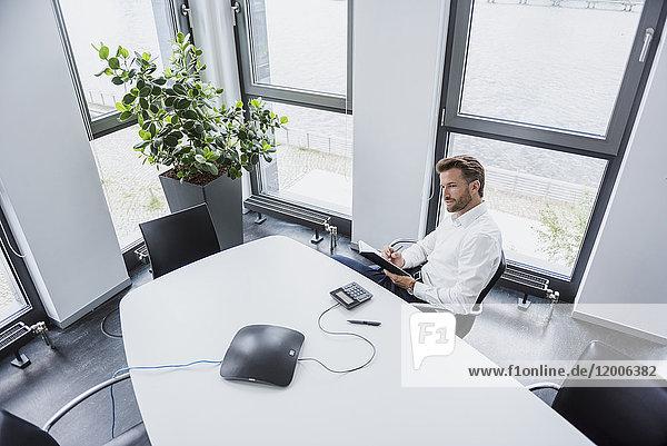 Geschäftsmann sitzt am Besprechungstisch in seinem Büro