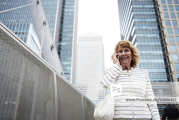 UK  London  lächelnde Senior-Geschäftsfrau am Telefon in der Stadt