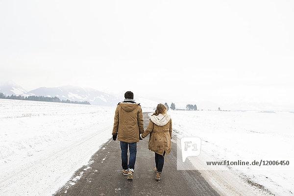 Rückansicht eines verliebten jungen Paares  das Hand in Hand auf einer Landstraße in einer verschneiten Landschaft wandert.