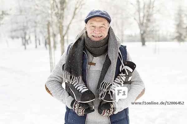 Lächelnder Senior mit Schlittschuhen im Winterwald