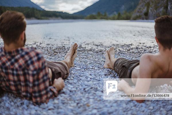 Deutschland  Bayern  Rückansicht von zwei Freunden  die am Flussufer liegen und die Ansicht betrachten