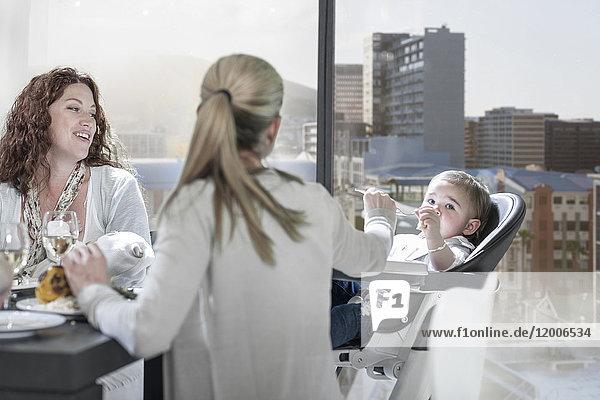 Mutter mit Freundin füttert Baby am Esstisch