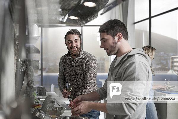 Freunde mit Weingläsern bei der Zubereitung einer Mahlzeit in der Küche