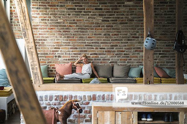 Reife Frau sitzend auf der Couch  Lesemagazin
