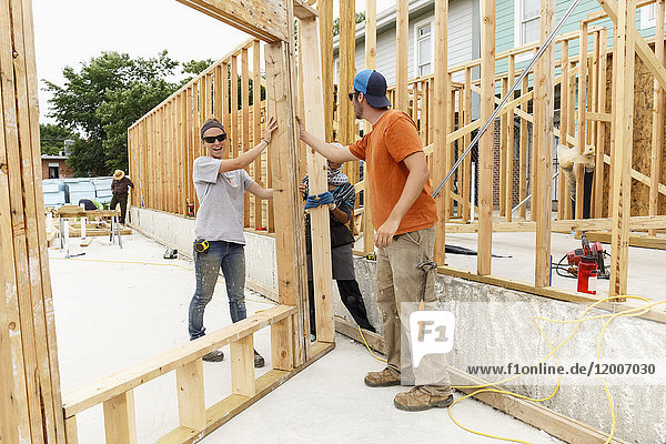 Volunteers holding framed wall at construction site