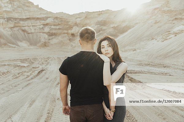 Middle Eastern couple hugging in the desert