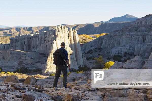 Caucasian man carrying backpack in desert
