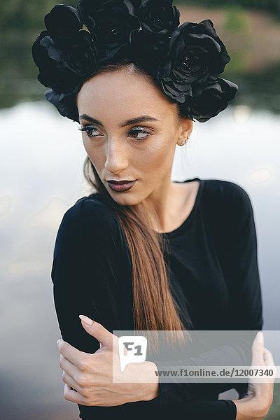 Close up of Middle Eastern woman wearing black dress near lake