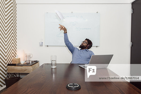 Black businessman wearing headphones throwing paper airplane
