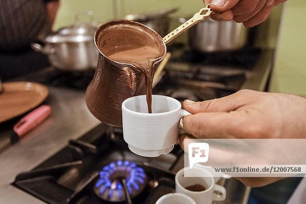 Server pouring espresso coffee into cup