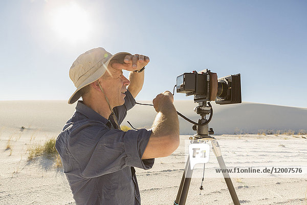 Caucasian photographer with tripod shielding eyes in desert